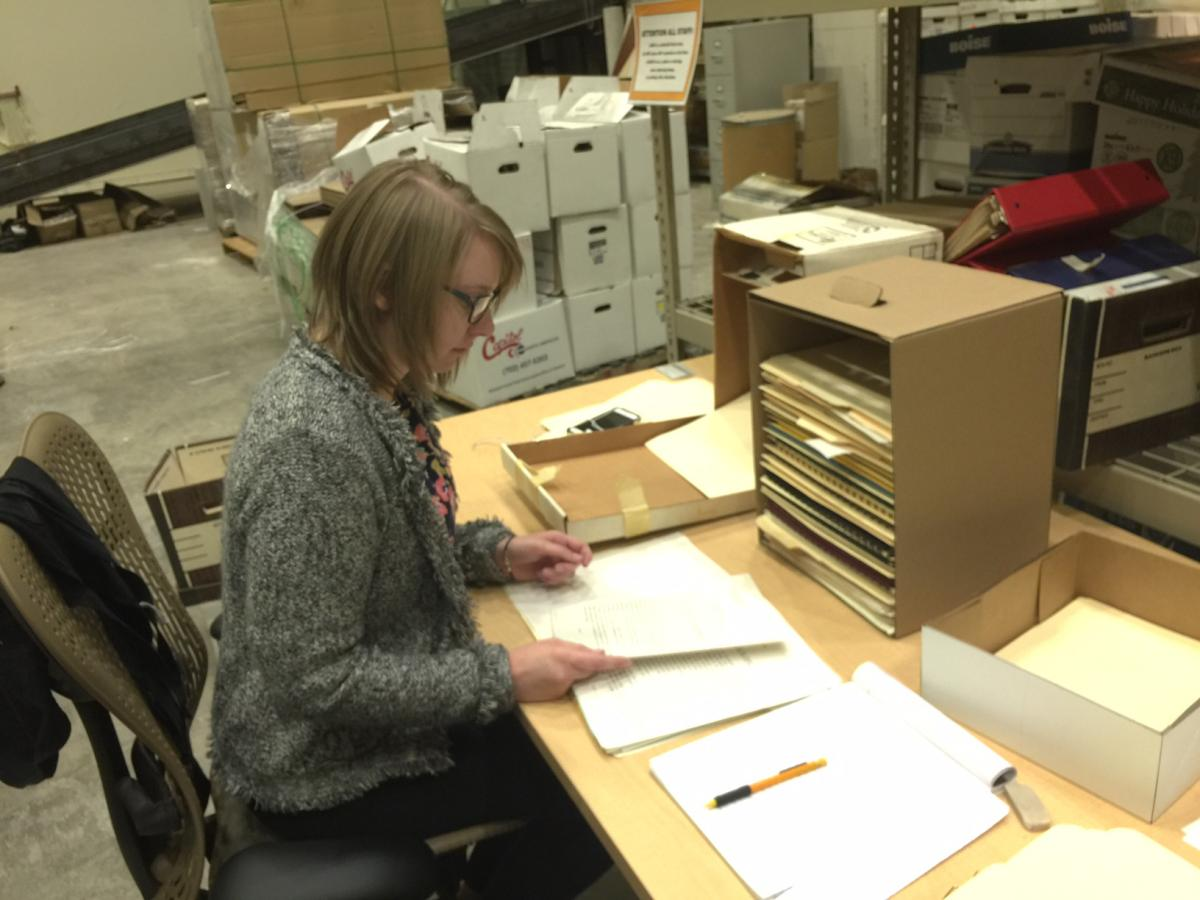 An archivists looks through papers and documents.