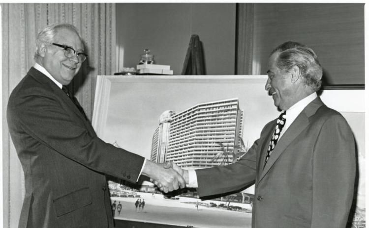 Morris Shenker, left, shaking hands with an unidentified man in front of an architectural drawing for the Dunes Hotel and Casino in Las Vegas, Nevada, circa 1950s