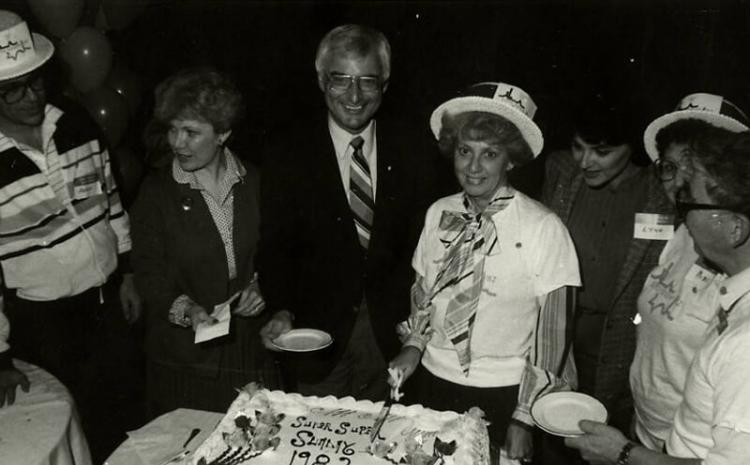 Cake cutting for Super Sunday event with Dennis Sabbath, Myrna Williams, Jim Santini, Dorothy Eisenberg (cutting cake), Lyn Rosencrantz, and Ray and Jerry Countess, 1982. MS-00731, Dennis and Roberta Sabbath Papers.