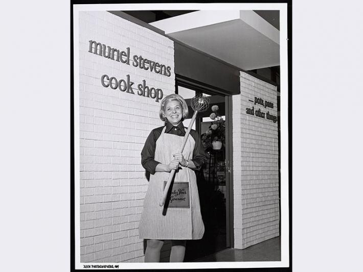 Muriel Stevens in front of her cook shop, circa 1975